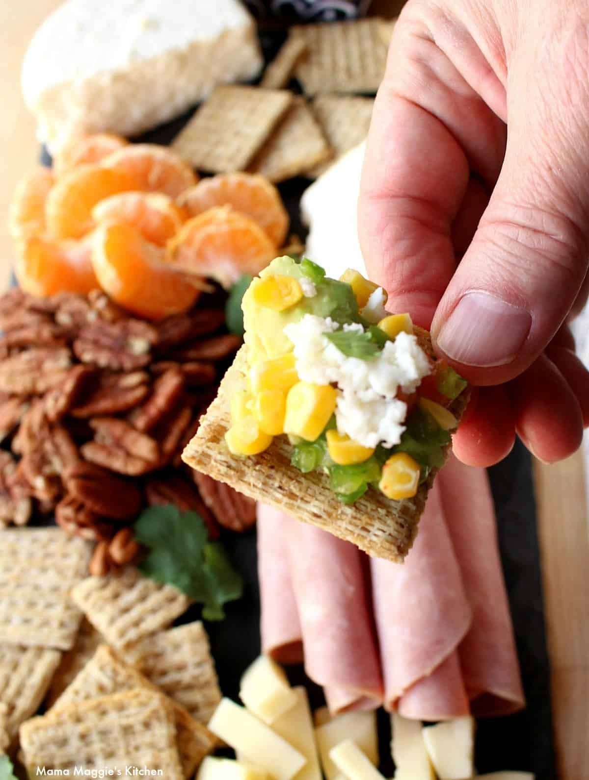 Hand holding a Triscuit with corn salsa.