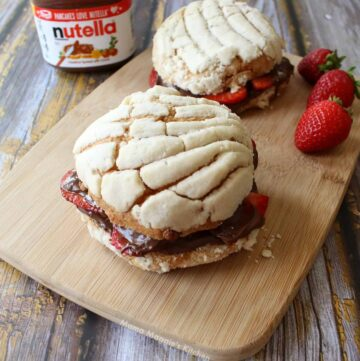 A picture of nutella stuffed conchas on a wooden cutting board next to an open container of nutella.
