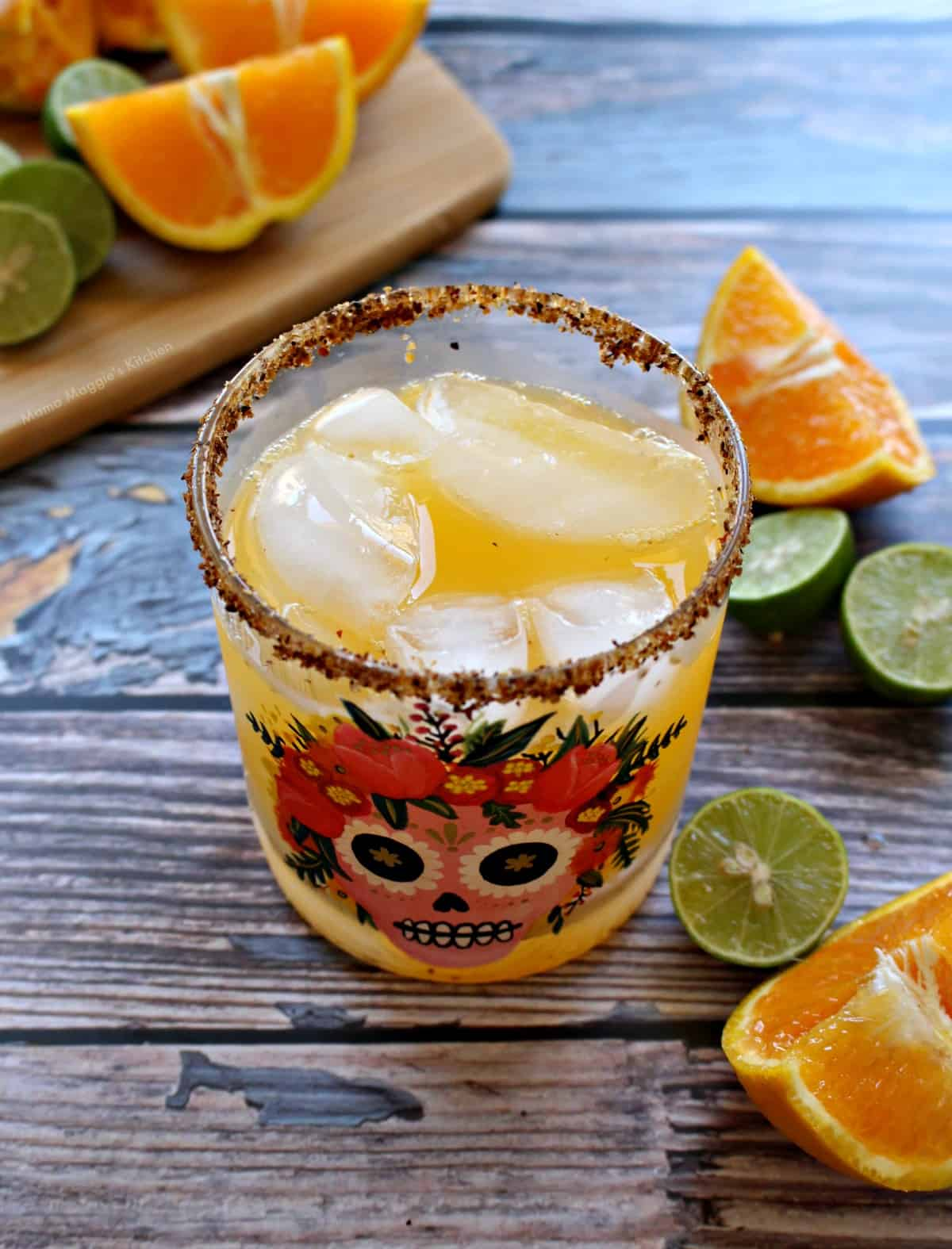 A glass with a Dia de Los Muertos skull on the front filled with Skinny Orange Margarita.