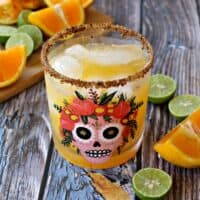 A skinny orange margarita in a glass decorated with a sugar skull and surrounded by lime and orange wedges.