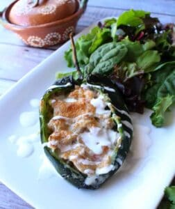 A pork chile relleno on a white plate drizzled with crema mexicana and next to a bed of lettuce.