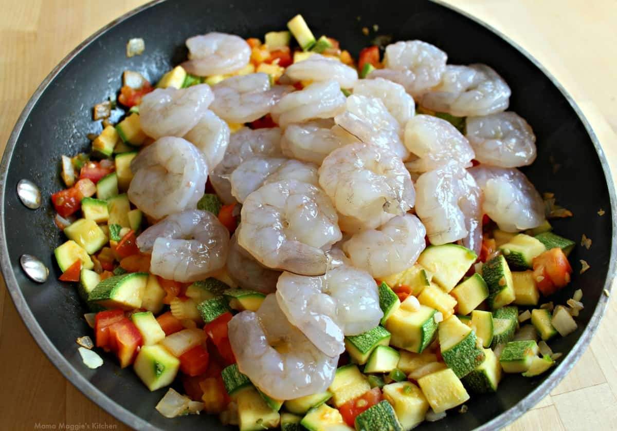 Raw shrimp cooking with the calabacitas in a skillet.