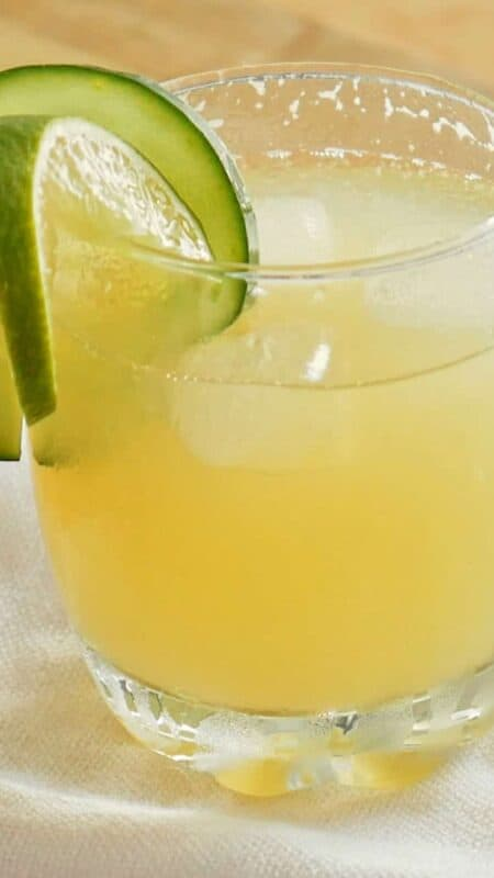 Spiked Agua de Pepino served in a glass and garnished with cucumber and lime slices.