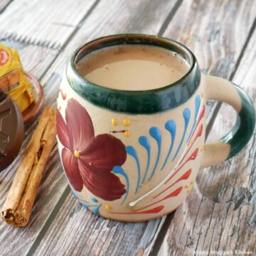 Atole de Chocolate served in a decorative Mexican cup next to a cinnamon stick.