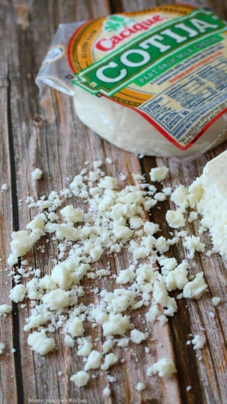 Crumbled cotija cheese next to a package of cheese.