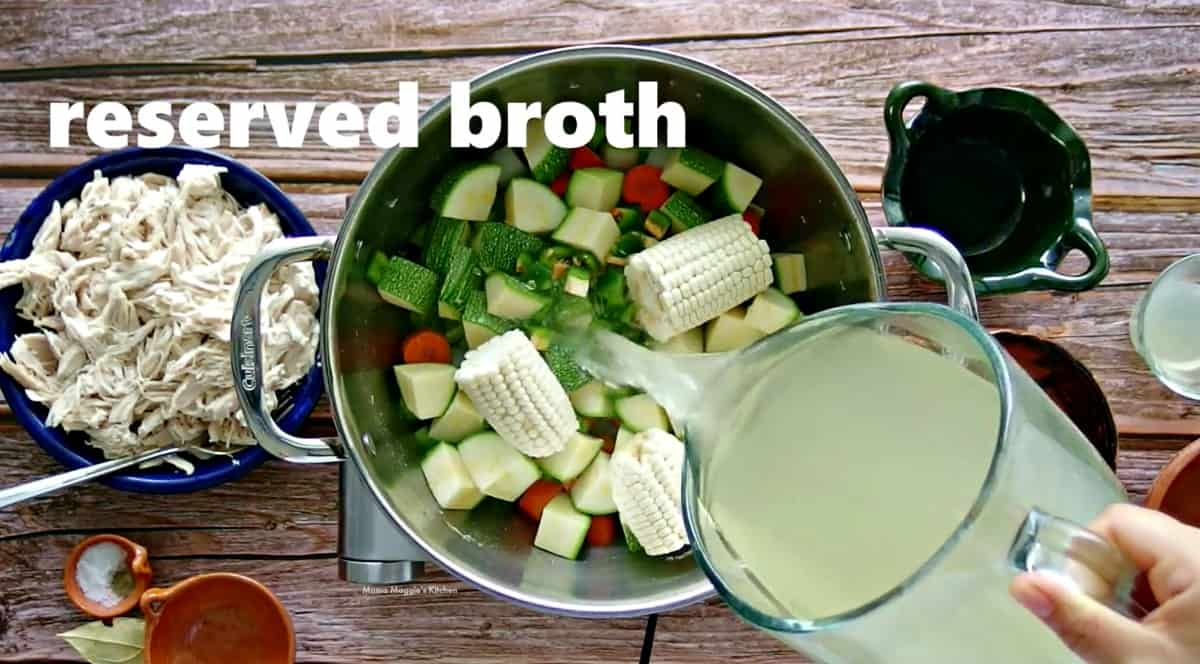 The reserved broth pouring into a pot with vegetables.