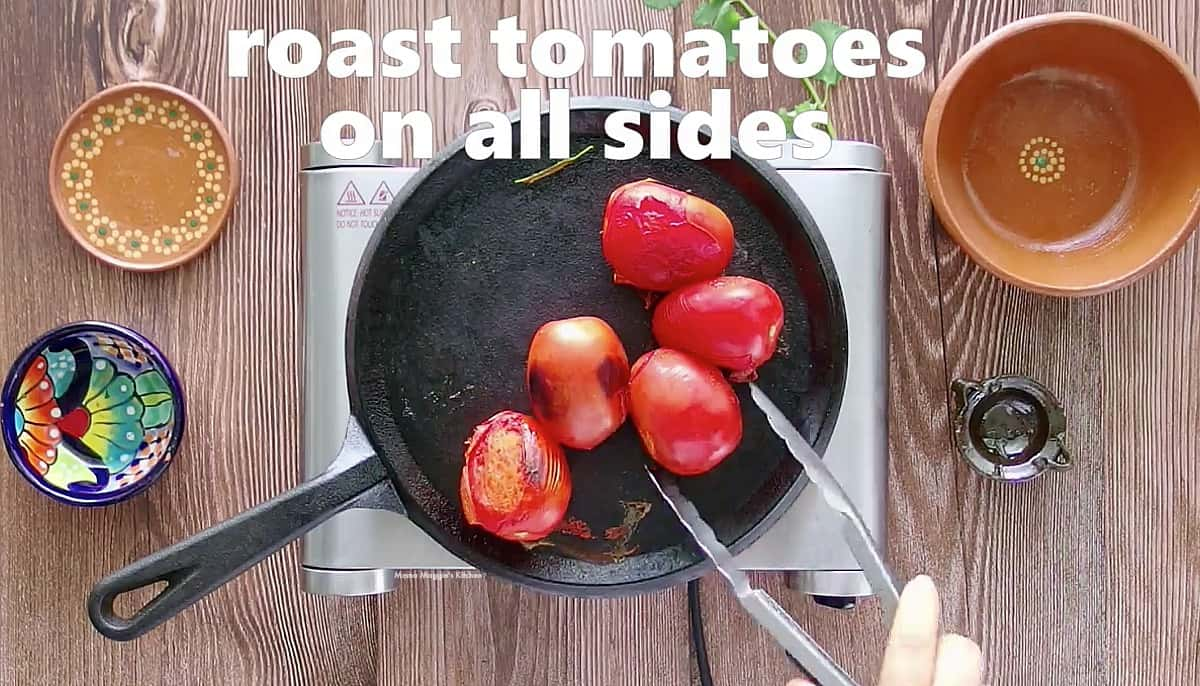 Tomatoes turning as they roast on a black skillet.