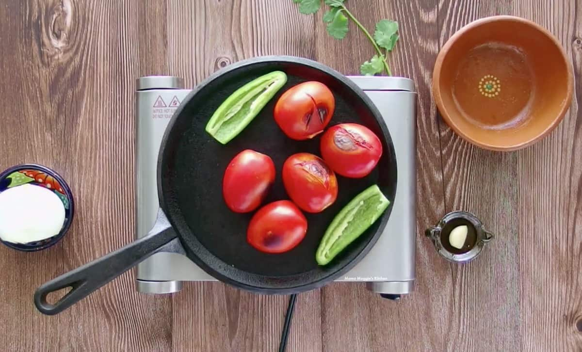 Tomatoes and jalapenos roasting on a black skillet.