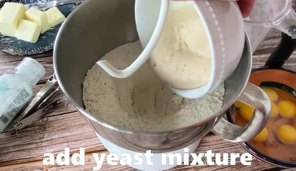 A bowl adding the yeast mixture to the KitchenAid bowl.