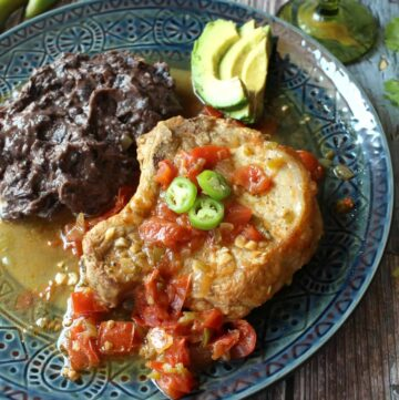 Chuletas a la Mexicana served on a blue plate next to black beans and stopped with serrano pepper slices.