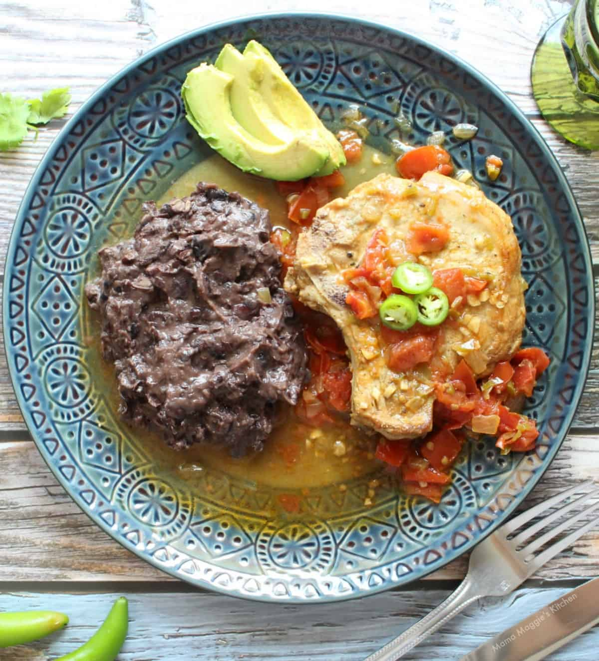 Mexican-Style Pork Chops served on a blue plate next to black beans and topped with serrano pepper slices.