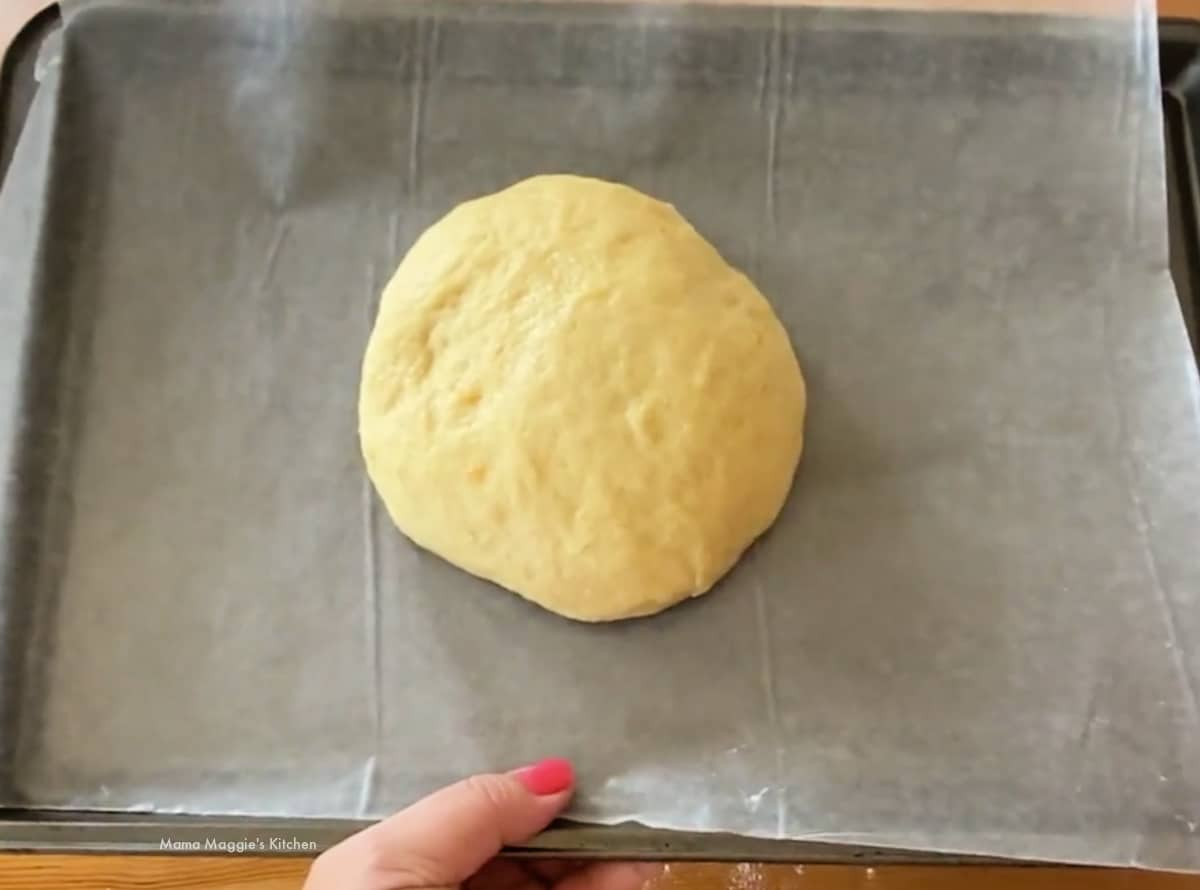 A bowl of dough on a lined sheet pan.