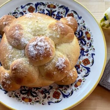 A picture of pan de muerto on a decorative plate next to a black and white picture and sugar skull.