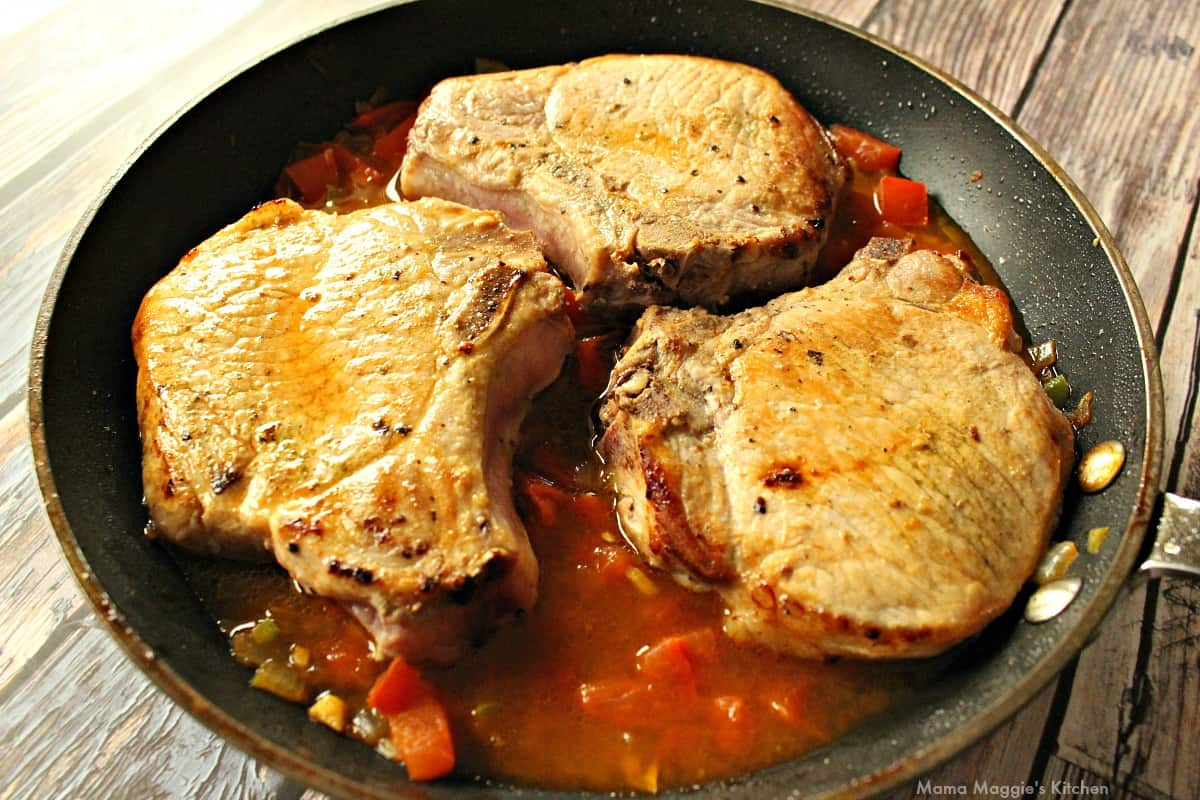 Seared pork sitting on top of the tomato mixture in a skillet.