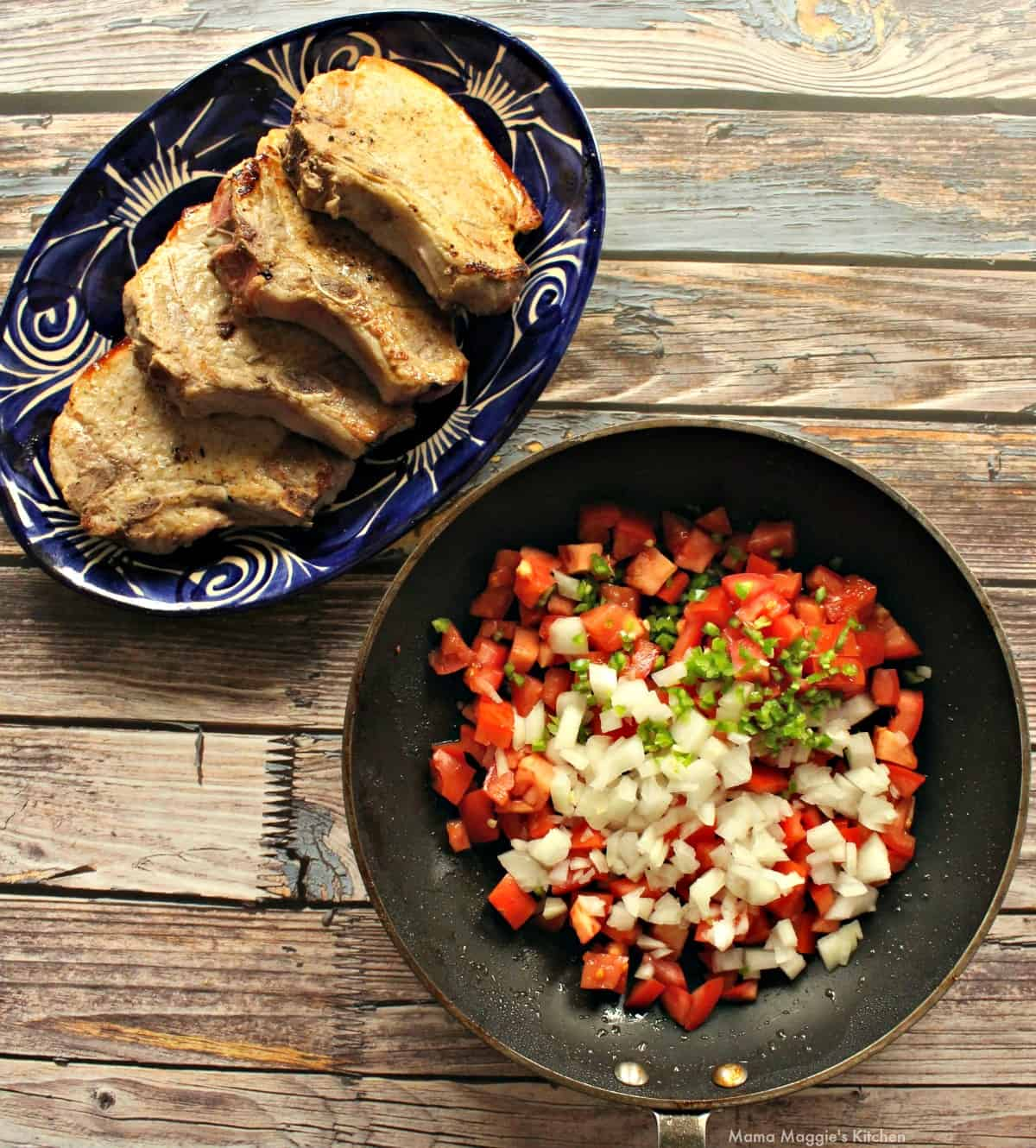 Seared pork chops on a blue plate next to a skillet with a tomato mixture.