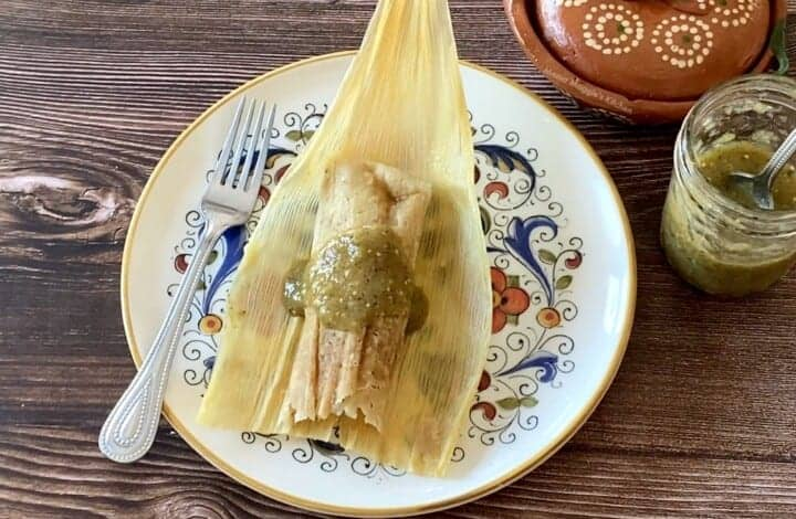 A chicken tamal on a corn husk and on a plate next to a fork and salsa.