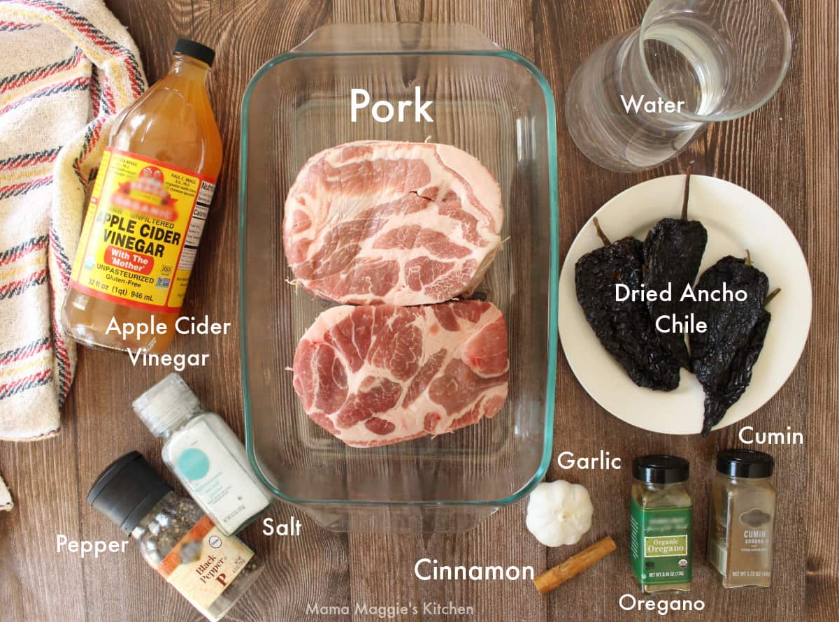 The ingredients for the ancho pork laid out and labeled on a wooden surface.