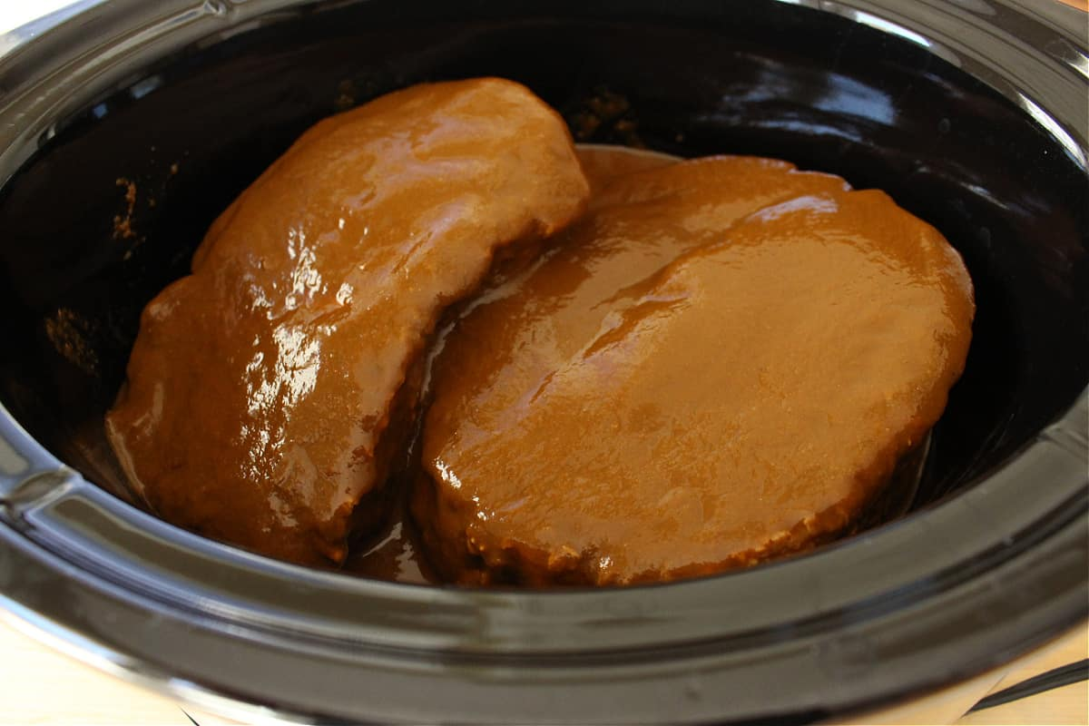 Pork roasts covered in ancho sauce in a slow cooker.