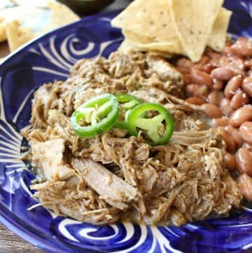 Slow Cooker Ancho Pork served on a blue plate and topped with jalapeno slices.