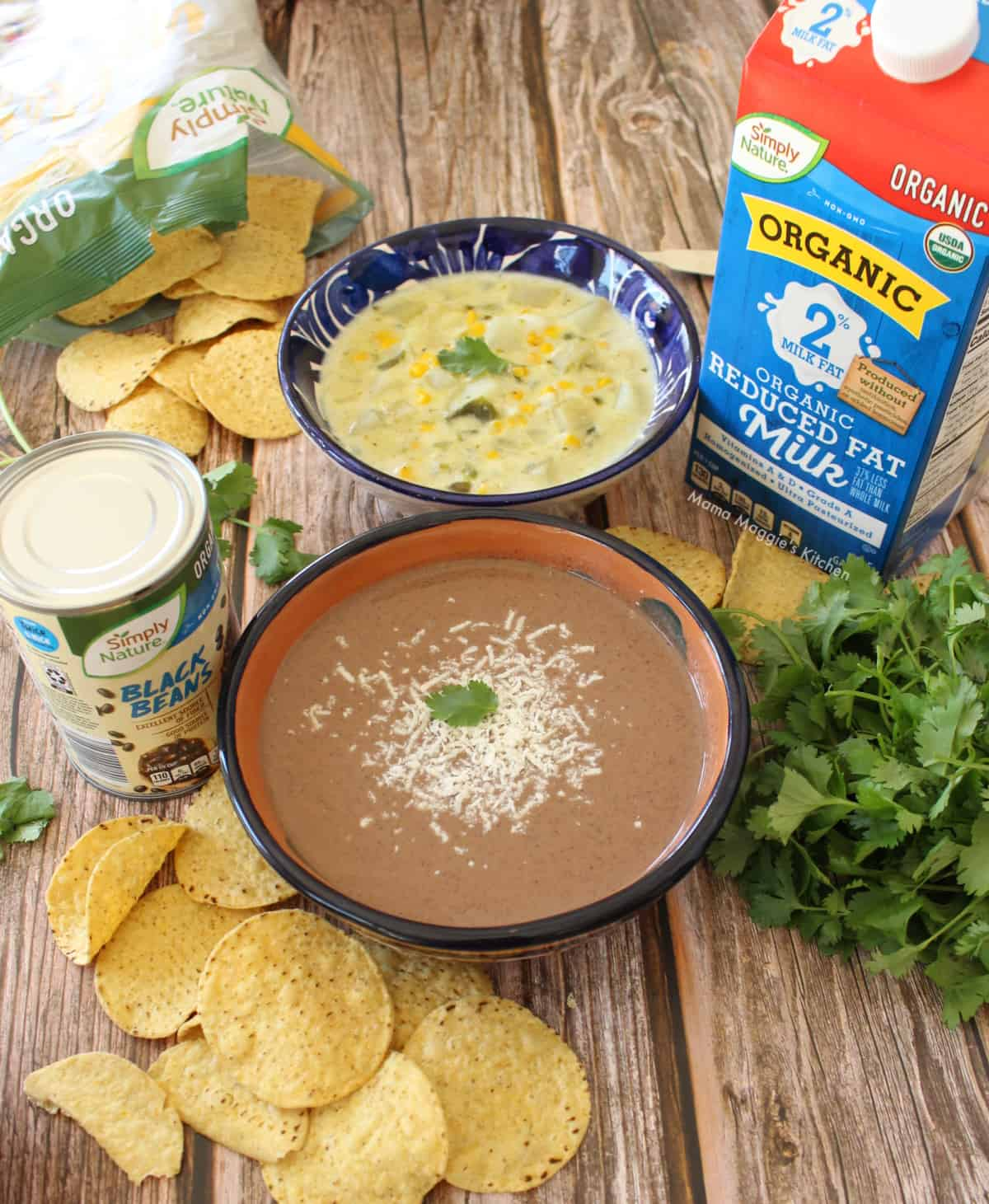 Crema de Frijol Negro and Caldo de Queso served in bowls and surrounded by chips and other ingredients.
