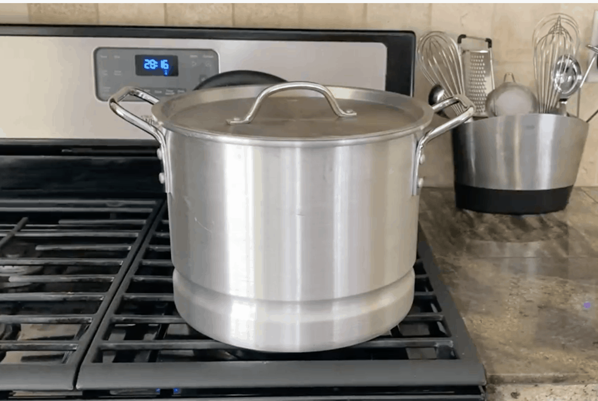 A steamer pot cooking on a stove.