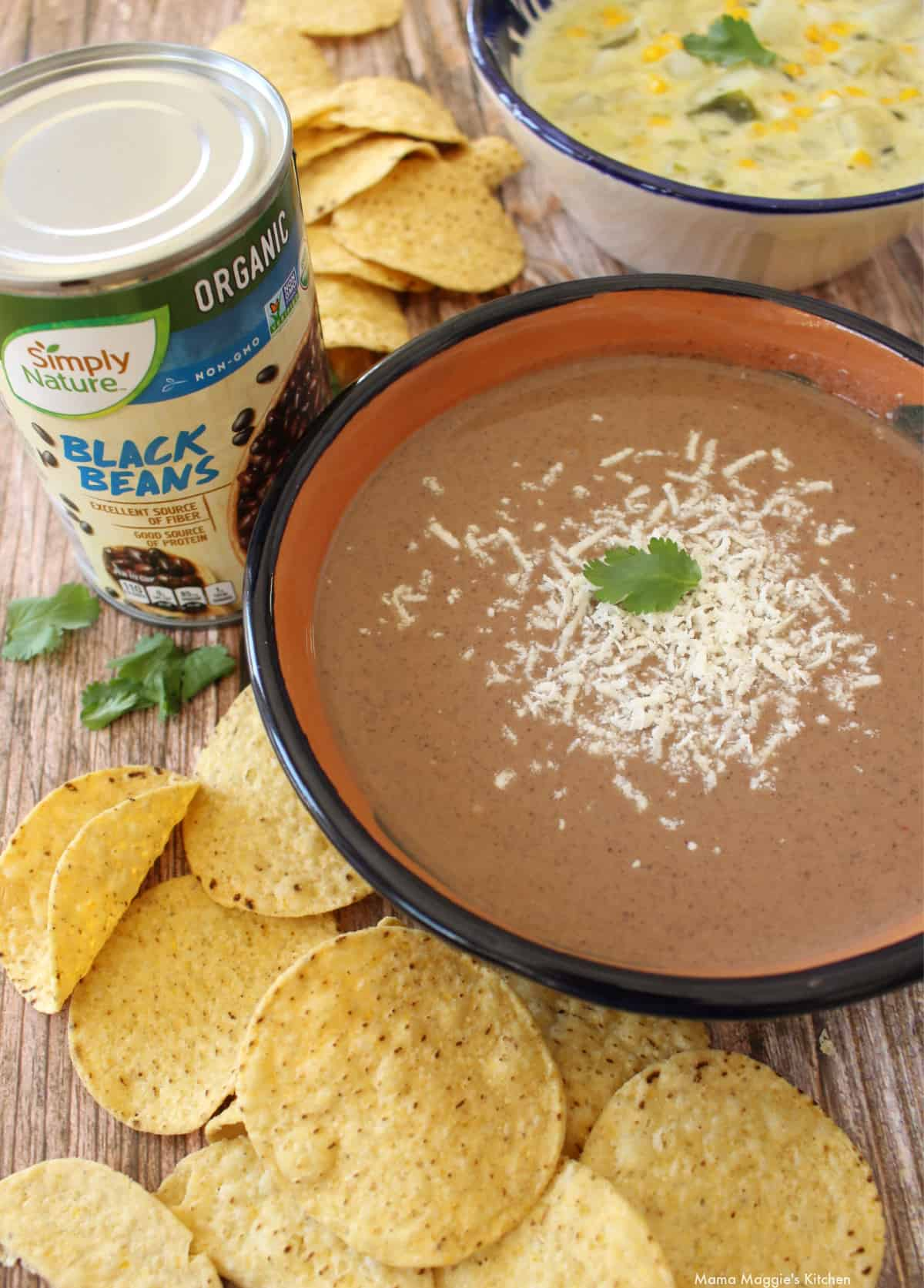A bowl of Crema de Frijol Negro next to chips and a can of beans.