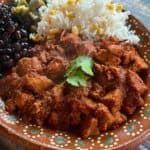 Asado de Puerco served on a decorative clay plate next to rice, beans, and nopales.