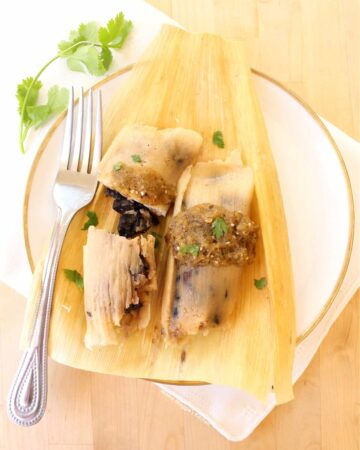 Two tamales on a corn husk topped with salsa, cilantro, and served with a fork.