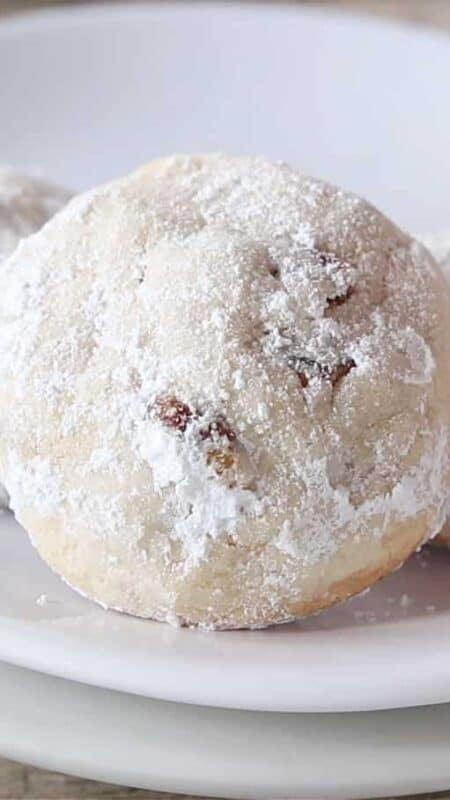 Three Mexican wedding cookies on a white plate.