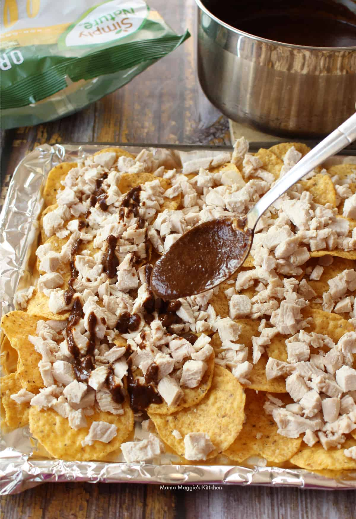 A spoon with mole sauce over a sheet pan with tortilla chips and chicken.