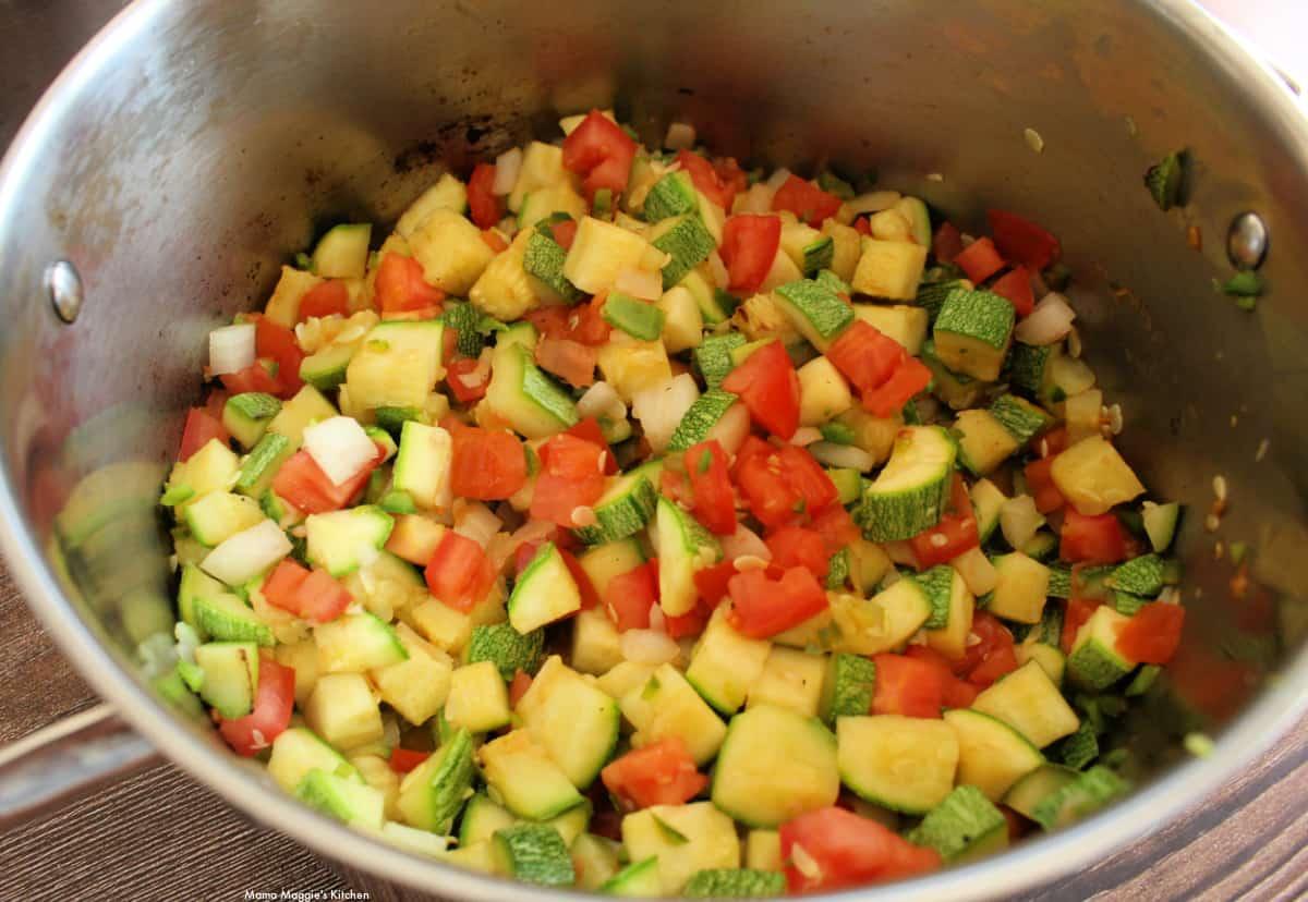 Calabacitas and tomatoes cooking a stock pot.