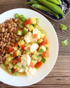 Calabacitas con Queso served on a white plate next to pinto beans.