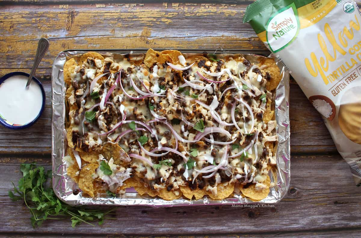Chicken Mole Nachos served on a sheet pan and next to sour cream, cilantro leaves, and a bag of chips.
