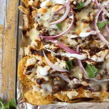 A sheet pan with Chicken Mole Nachos topped with red onion slices.