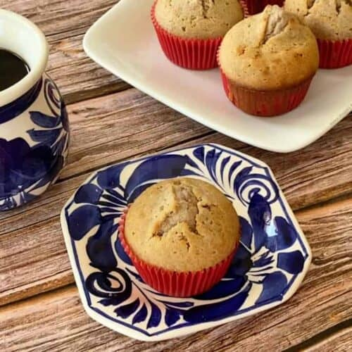 A mantecada Mexican muffin served on a blue plate and next to a cup of coffee.