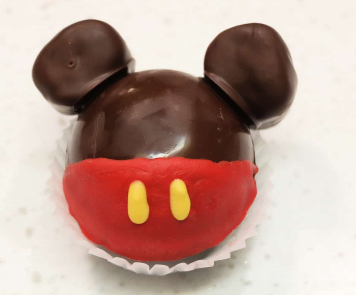 A Mickey Mouse Hot Chocolate Bomb fully assembled and drying on a white cupcake liner.