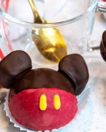Two Mickey Mouse Hot Chocolate Bombs next to each other next to cocoa mix and a cup.