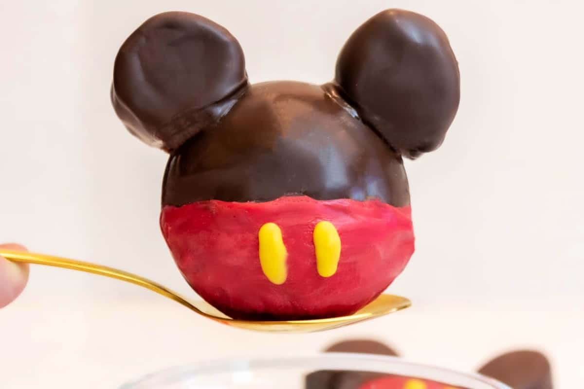 A spoon holding a Mickey Mouse Hot Chocolate Bomb.