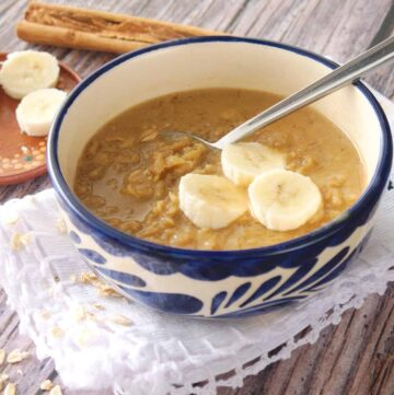 Mexican avena served in a blue bowl and topped with banana slices.