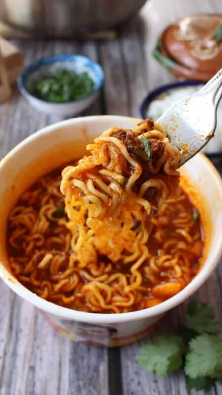 A fork holding birria ramen surrounded by the toppings.