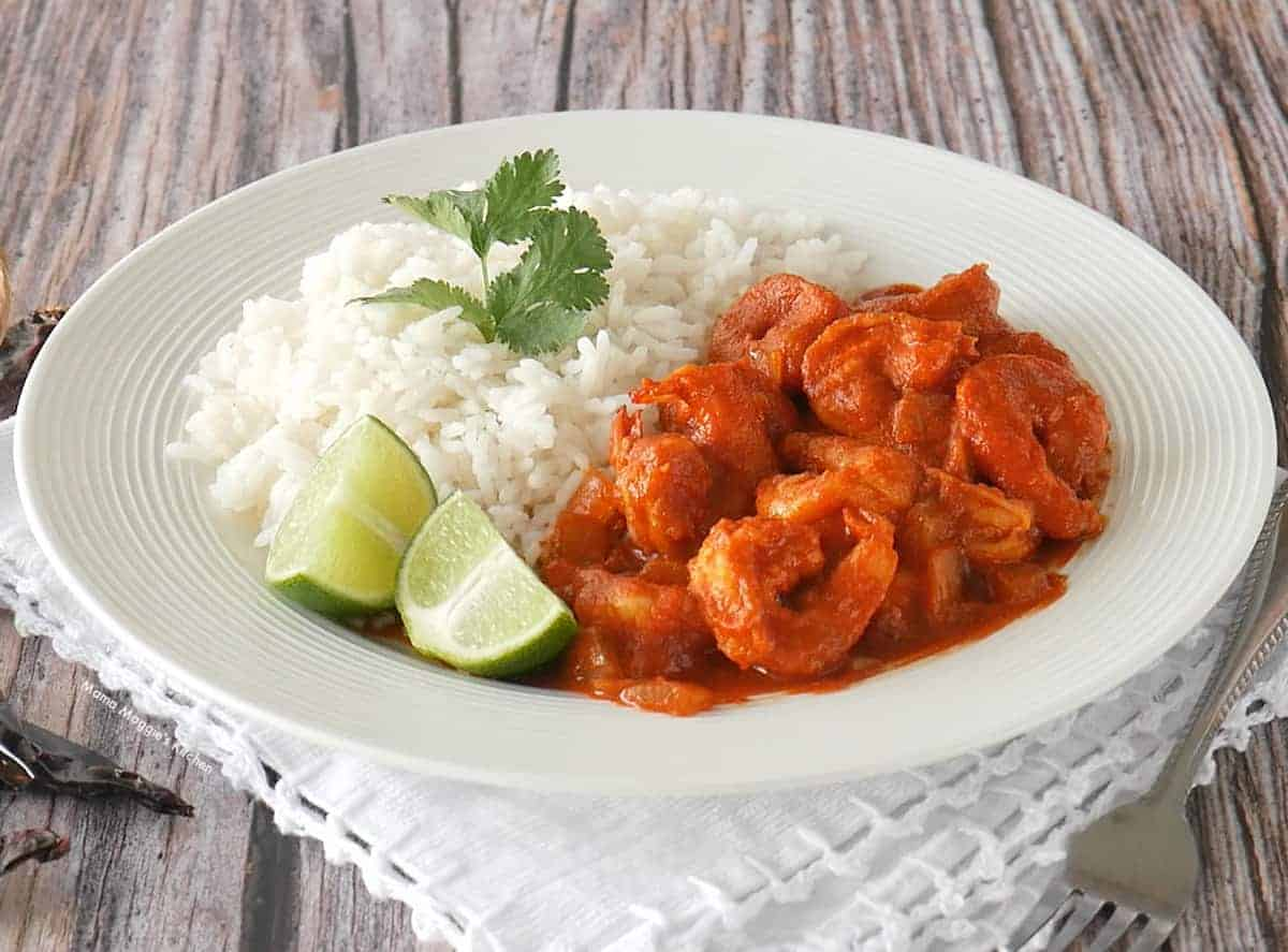 Camarones a la Diabla served next to white rice and lime wedges.