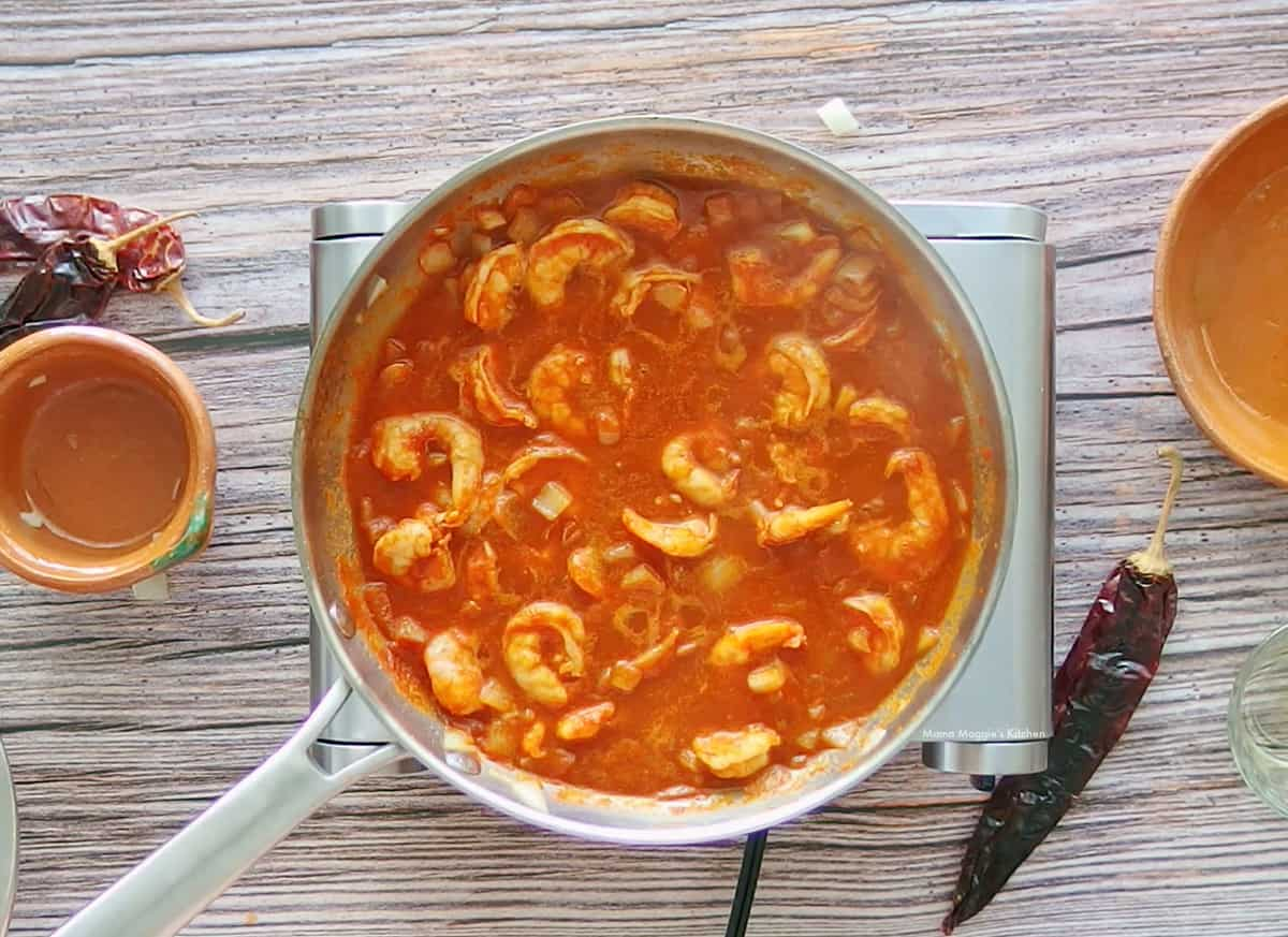 Shrimp cooking in a red chile sauce in a skillet.