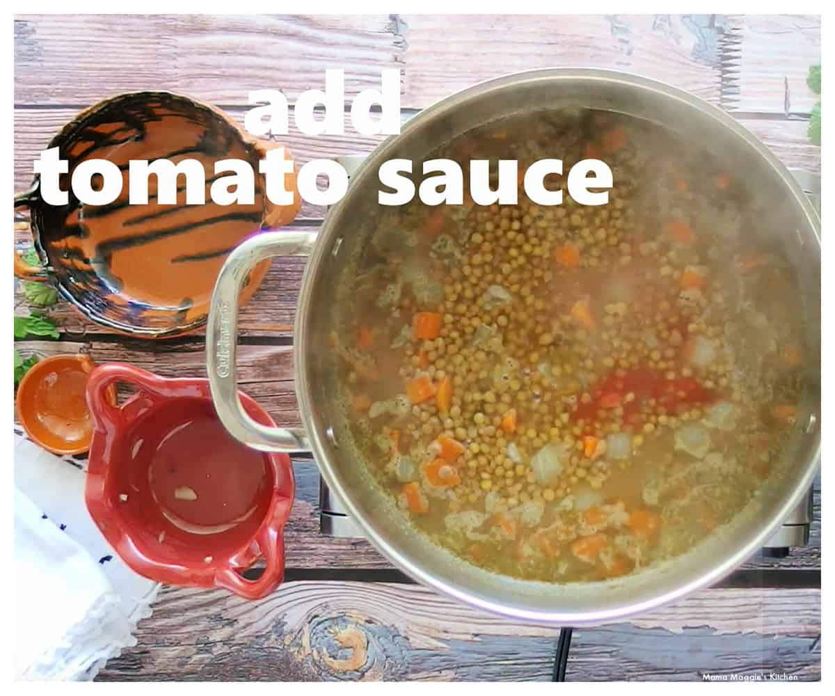 A pot of lentil cooking with tomato sauce.