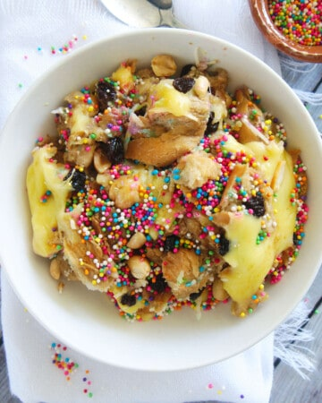 Capirotada (or Mexican Bread Pudding) served in a white bowl and topped with sprinkles.