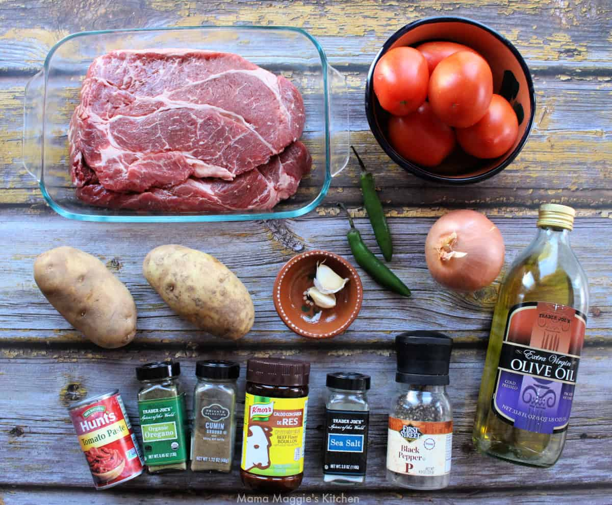 The ingredients for carne con papas laid out on a wooden table.