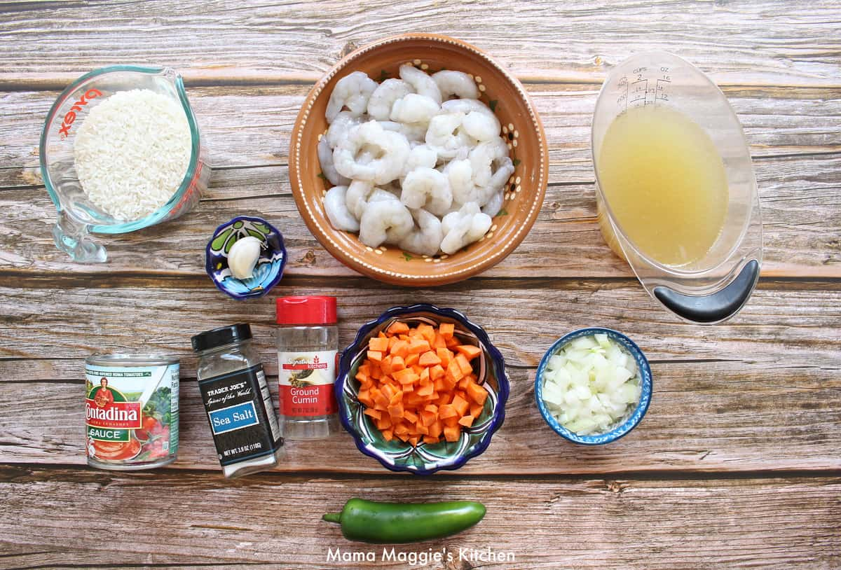The ingredients needed to make Arroz con Camarones laid out a wooden surface.