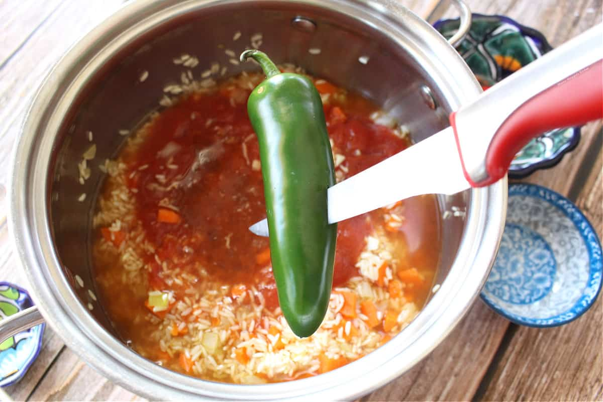 A knife slicing through a jalapeno over a stock pot.
