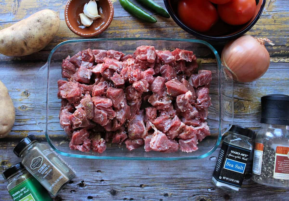 Raw beef chopped into 1-inch pieces on a glass baking dish and surrounded by spices.