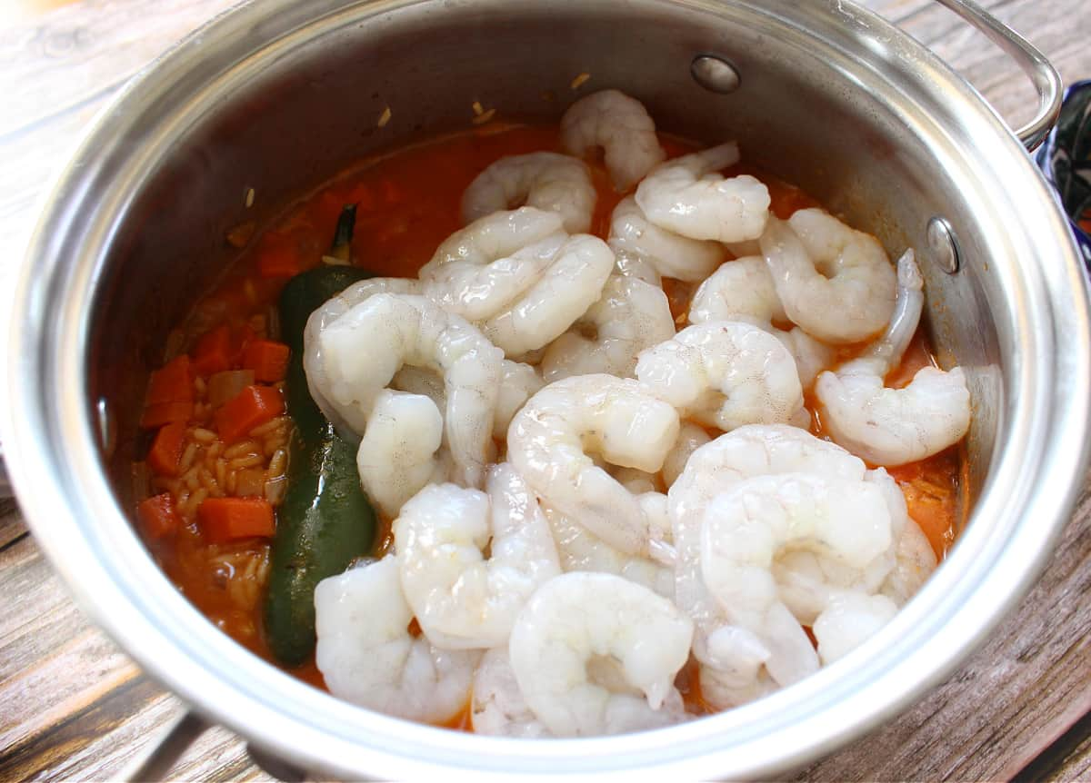 Raw shrimp in a stock pot with rice and jalapeno.