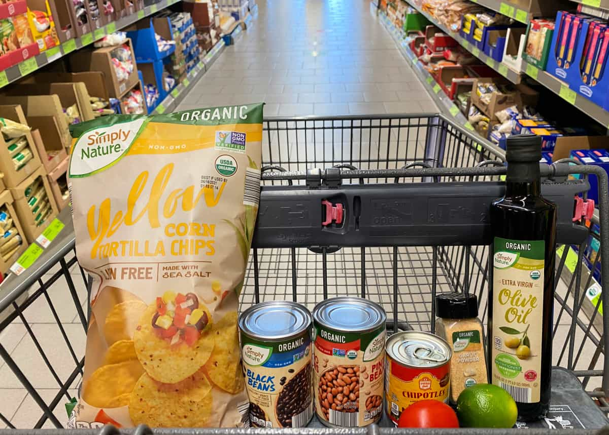 A shopping cart with items inside of a grocery store.